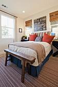 Schlafzimmer mit Doppelbett und antiker Bettbank aus Holz