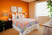 Interior of tidy bedroom with orange accent wall; Azusa; California; USA