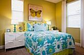 Schlafzimmer in Grün- & Blautönen mit Bett, Tagesdecke, Nachtschränkchen & Wandbild