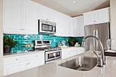 Moderne weisse Küche mit türkisfarbenen Wandfliesen als Farbakzent