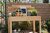 Potted plants and gardening tools on wooden table in backyard