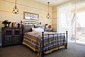 Schlafzimmer mit Metallbett und Schränken als Nachtkonsolen