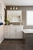 Bathroom with tiled bathtub and white cabinets