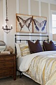 Butterfly paintings over bed with pendant light in contemporary bedroom