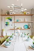 Esszimmer mit Regal, moderner Hängeleuchte & Esstisch dekoriert mit Pflanzen & Kerzen