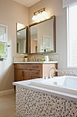 Bathtub, cabinet and mirror in bathroom