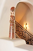 Statue, balustrade and lit wall lamp in background; Santa Fe; New Mexico; USA