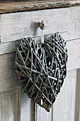 Deko-Herz aus Weidenzweigen hängt an Knopf von Schublade