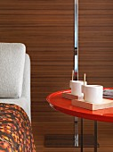 Coffee cups on red table by chaise longue in hotel room