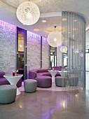 Moderner Lounge-Bereich eines Nachtclubs mit kugelförmigen Deckenleuchten, Ledercouchen & Sitzhockern