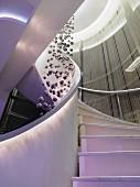 Beleuchtete Wendeltreppe eines Luxus-Hotels mit Fadenvorhängen & Dekoobjekt aus Kugeln