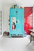 Reflection of woman washing dishes in kitchen in mirror on blue cupboard door