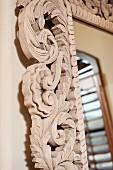Aufwendig geschnitzter Holzrahmen eines Wandspiegels (Nahaufnahme)