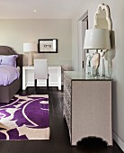 Bedroom in shades of gray with purple accents, bed, dressing table & silver chest of drawers