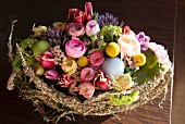 Easter arrangement in wicker basket with half-moons of hay & spring flowers