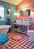 Bathroom with free-standing bathtub on red and white chequered floor and twin basin on ornate metal washstand