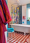 Bathroom with free-standing bathtub on red and white chequered floor; towels on metal chair