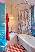 Colourful shower curtain on round curtain rail above retro bathtub; chandeliers and mixture of blue and white tiles in background