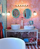 Basins on ornate metal washstand against toile de jouy wallpaper with blue-tiled wall to one side