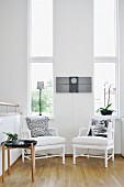 White armchairs and side table against wall with tall, narrow windows