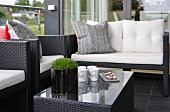 Elegant outdoor furniture made from black all-weather wicker on black tiled floor