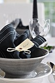 Black napkin with name tag in grey ceramic dish with matching plate