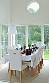 White, upholstered chairs around festively set dining table in front of glass walls
