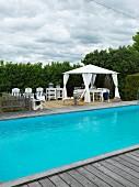 Pool mit Holzeinfassung im Garten, im Hintergrund zeltartiger Pavillon und Sonnenliegen