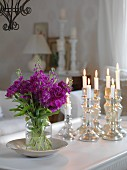 Vase of purple garden flowers and lit candles in silver candlesticks on table