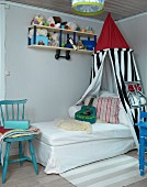 Child's bed below canopy in corner