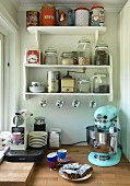 Retro kitchen appliance and espresso machine on worksurface below shelves of storage jars