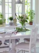 weiße Stühle um Esstisch mit Rhabarber und Flieder im Esszimmer