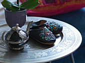 Leather slippers embroidered with sequins and Oriental teapot on Moroccan tray table