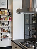 Gas cooker next to glass-fronted cabinet; colourful tea caddies and spice jars on wall-mounted shelves