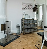 Antique, white tiled oven and shelving on castors with metal boxes in dining room of period apartment