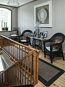 Black wicker chairs ad framed photos on console table on landing with old wooden balustrade