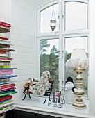 Dolls, Moomin figurine and framed picture on window sill next to bookshelves