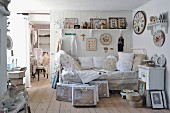 Daybed with lace cushions below collection of vintage clocks on white wooden wall and vintage-style ornaments on bracket shelf