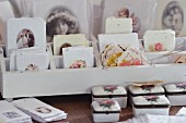 Rose-patterned, china boxes in front of white wooden rack of vintage gift tags