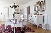 Antike, weisse Esszimmermöbel im Landhausstil, an Wand Sideboard vor Bildersammlung