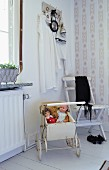 Vintage dolls' pram and white folding chair in corner of room with striped wallpaper