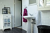 Pedestal sink against white-tiled wall in vintage-style bathroom