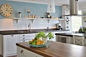 Country-house kitchen with white base units, white-tiled splashback and wall painted pale blue
