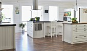 Spacious, white, country-house-style kitchen with free-standing island counter under stainless steel extractor hood