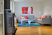 Pale grey, designer sofa set, pale blue rug, modern artwork in shades of red and wood-burning stove in foreground