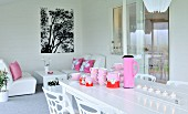 Pink crockery, thermos flask and lit tealights on white table in front of comfortable lounge area