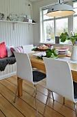 Retroleuchte über Tisch im Esszimmer mit weisser Holzverkleidung an der Wand