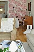 Blick vom Sitzbereich mit Polstermöbeln auf ein Klavier und Tapete mit Toile-de-Jouy Muster