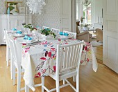 Table festively set with floral tablecloth in white dining room