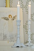 White candlesticks and picture of angel in front of wallpaper with pattern of delicate climbing plants